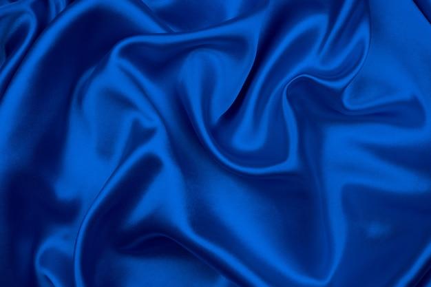 De vlotte elegante blauwe zijde of satijntextuur kan als abstracte achtergrond gebruiken.
