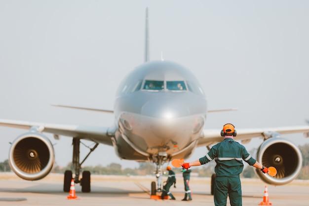 De vluchtingenieur van het vliegtuigonderhoud toont parkteken voor het landen van het vliegtuig
