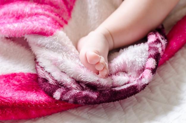 De voet van de aziatische pasgeboren baby op het bed