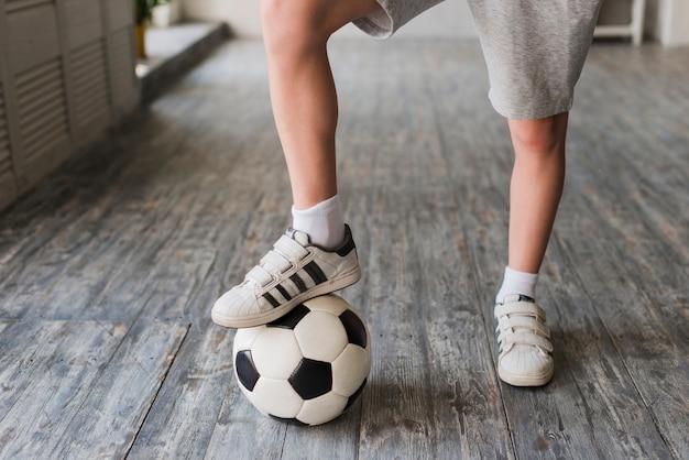 De voet van de jongen op voetbalbal over de hardhoutvloer