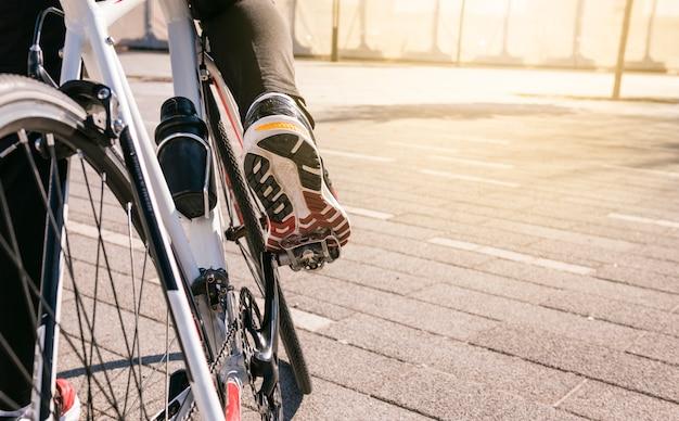 De voet van de mannelijke fietser op fiets pedaal berijdende fiets in openlucht