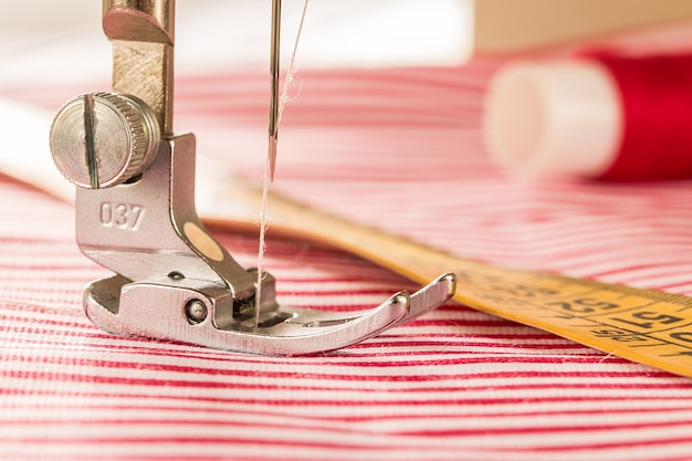 De voet van de naaimachine met een naald naait stof