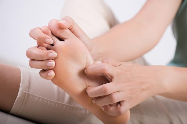 De voet van de vrouw krast thuis de jeuk met de hand. gezondheidszorg en medisch concept.