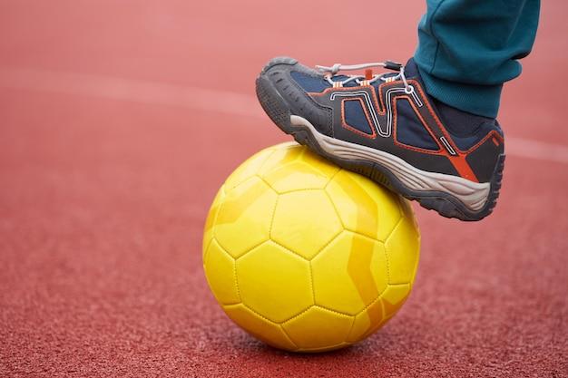 De voet van het jonge geitje, die een voetbalbal op een schoolspeelplaats houdt, sluit