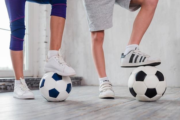 De voet van het meisje en van de jongen op voetbalbal