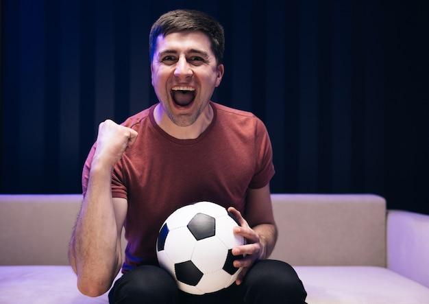 De voetbalfan van de jonge leuke kerel vrolijkt steun favoriete team op houdt voetbal in rode t-shirt