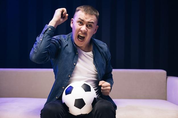 De voetbalfan van de jonge leuke kerel vrolijkt steun favoriete team op houdt voetbal vast