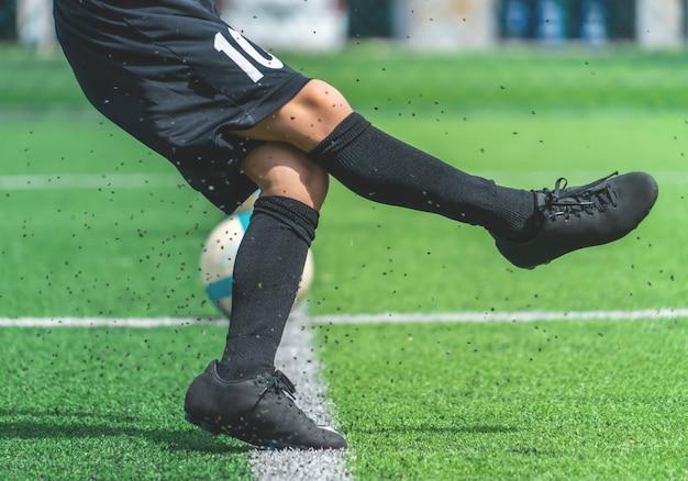 De voetbaljongen leidt het schoppen van de bal op voetbal opleidingsgebied op