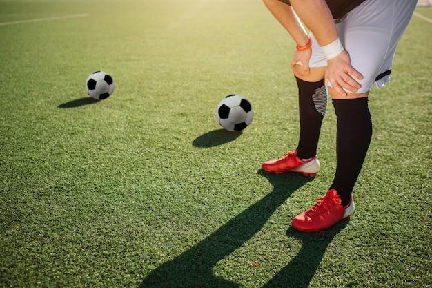 De voetballerstribune op groen gazon en houdt handen op knieën. het is zonnig buiten. twee voetbalballen die verder op gazon liggen.