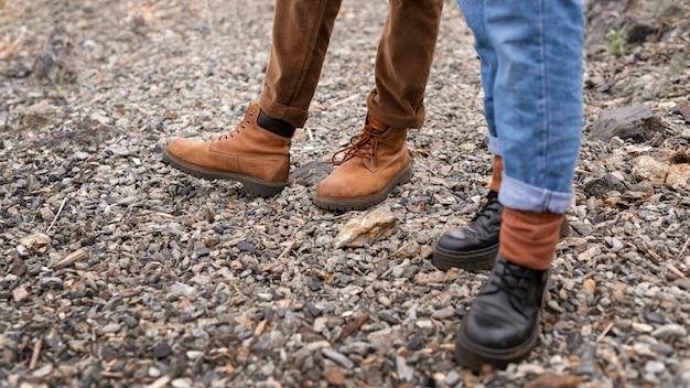 De voeten die van het paar zich op grind bevinden