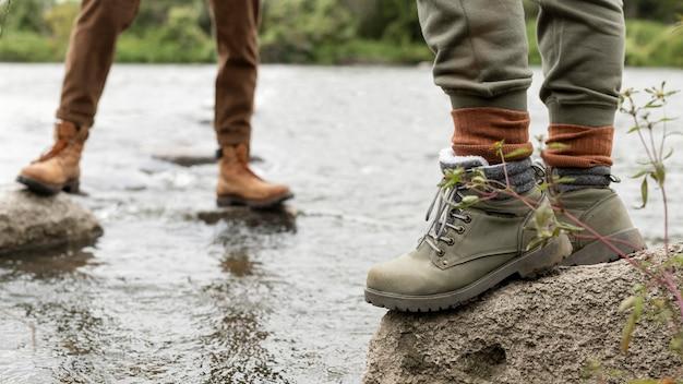 De voeten die van het paar zich op rotsen bevinden