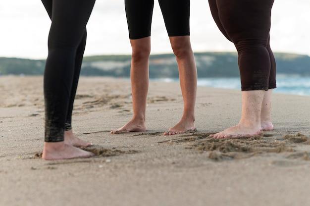De voeten van close-upvrienden op zand