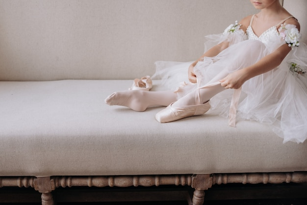De voeten van de balletdanser op studiovloer. tienerdanser trekt ballet pointe-schoenen aan