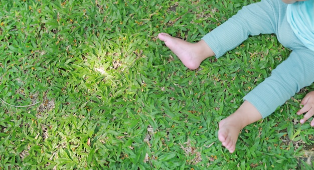De voeten van de close-upbaby zitten op het groene gazon. boven weergave.