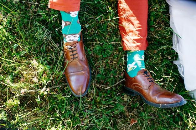 De voeten van de mens in leren schoenen en groene sokken liggen over het gazon