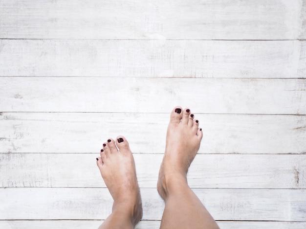 De voeten van de selfievrouw met donkerrode spijkers op witte uitstekende houten witte achtergrond.