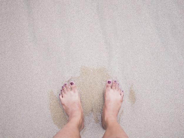 De voeten van de selfievrouw op de achtergrond van het de zomerstrand.