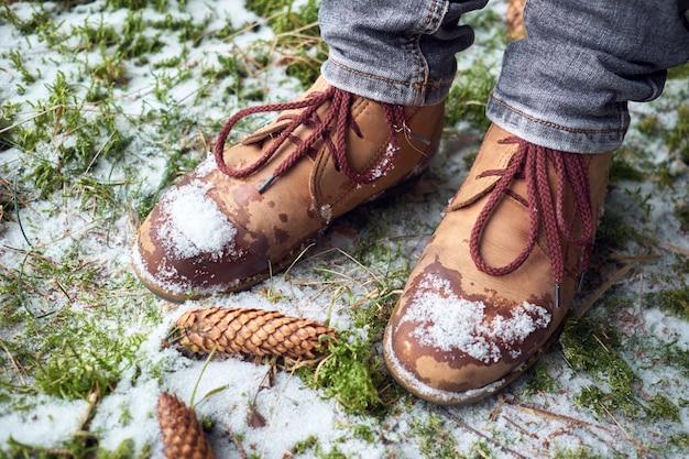 De voeten van de vrouw in reislaarzen op een bemoste sneeuwgrond in de winterbos. reizen concept.