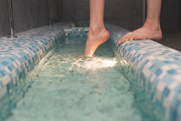 De voeten van de vrouw op de rand van badkuip