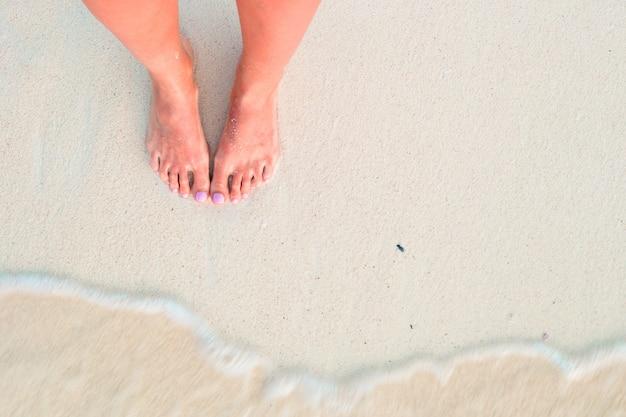 De voeten van de vrouw op het witte zandstrand in ondiep water