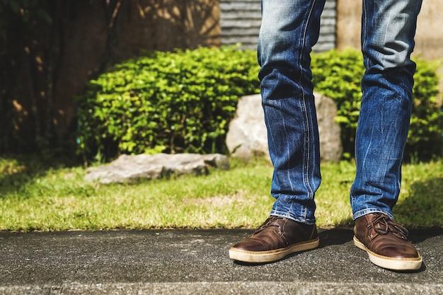 De voeten van een alleenstaande man permanent op de grond dragen van jeans