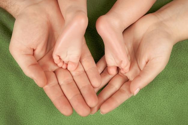 De voeten van een pasgeboren baby liggen in de armen van zijn ouders