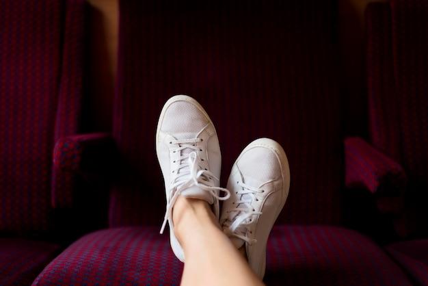 De voeten van het close-upmeisje op treinzetel