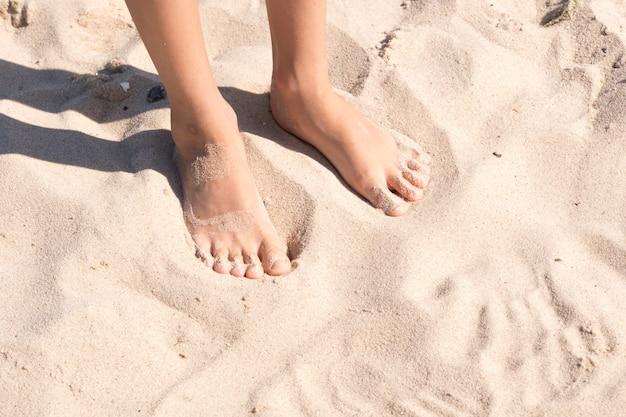 De voeten van het kind in het zand
