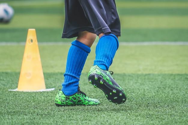 De voeten van het kind oefenen rennen en bewegen op voetbalveld