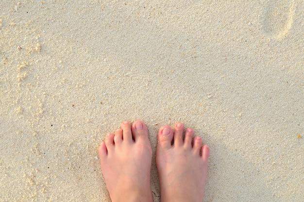 De voeten van het meisje in het zand op het strand