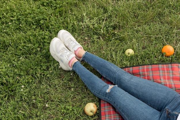 De voeten van het meisje op een picknickdeken