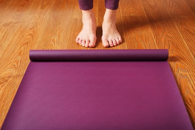 De voeten van het meisje staan voor een uitgevouwen yogamat op de houten vloer. yogalessen, asana-oefeningen