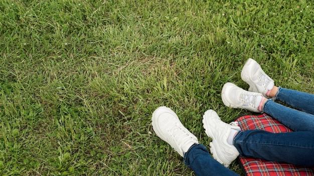 De voeten van het paar op een picknickdeken