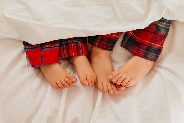 De voeten van kinderen in bed op eerste kerstdag