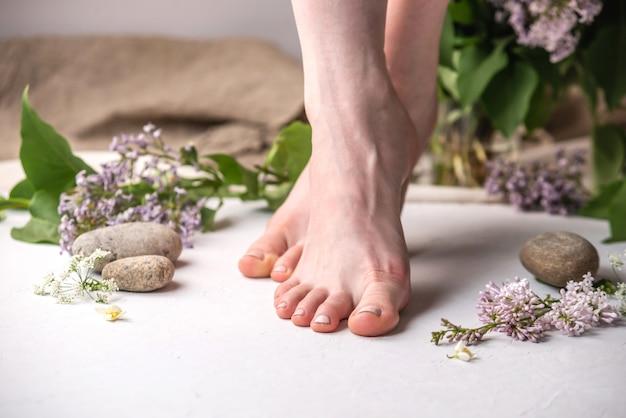 De voeten van verzorgde vrouwen met beige nagellak op een witte achtergrond met bloemen en stenen