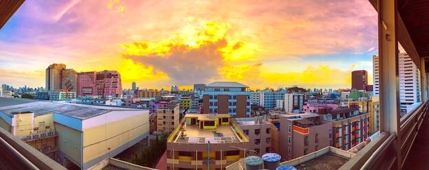 De vogelmening van het panorama over stad met zonsondergang en wolken in de avond