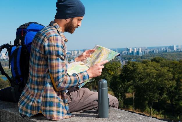 De volgende route kiezen. geconcentreerde jonge man zit in de buurt van rugzak en kijkt door een kaart