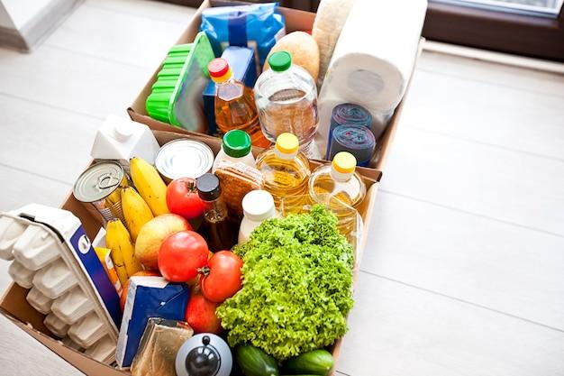 De volle kartonnen ecodoos met producten uit de supermarkt op de grond thuis bij de deur