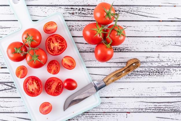De volledige en halve tomaat op witte snijplanktomaat vertakt zich dichtbij het snijplankmes op witte houten oppervlakte