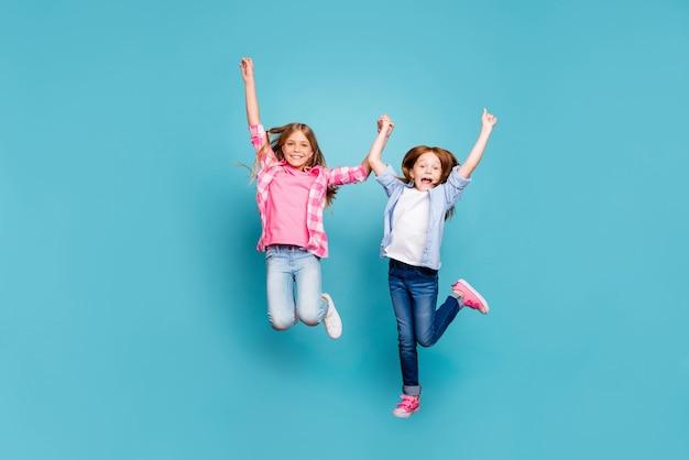 De volledige foto van de lichaamsgrootte van twee dolgelukkige meisjes die gek van geluk zijn die het wit van het jeansdenim met opgeheven handen dragen terwijl geïsoleerd met blauwe achtergrond
