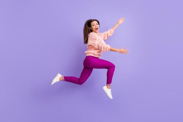De volledige foto van het lengteprofiel van dame die hoog het haasten springt steekt handen op paarse muur op