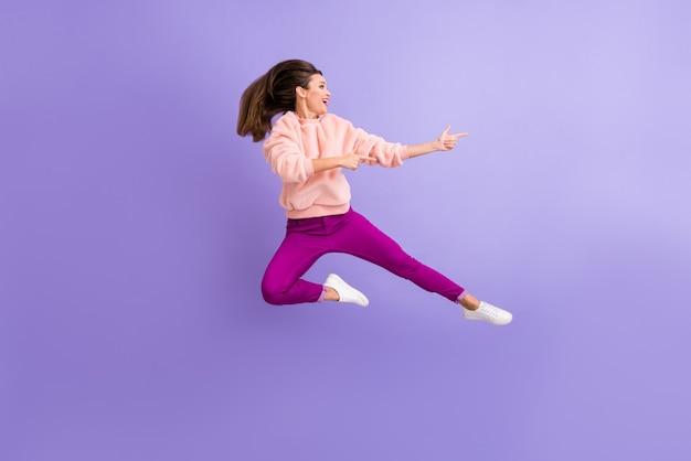 De volledige foto van het lengteprofiel van dame die hoog springt, wijzend op de lege ruimte van de vingers
