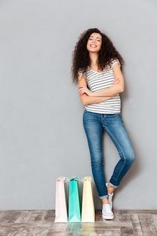 De volledige grootte van trendy vrouw die na het winkelen rusten en van haar aankopen genieten terwijl status met wapens vouwde grijze muur over