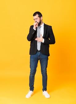 De volledige lengte bedrijfsmens over geïsoleerde gele muur lijdt aan hoest en voelt slecht
