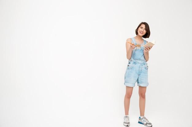 De volledige lengte ernstige vrouw schrijft in notitieboekje neer