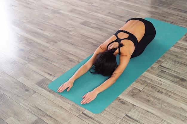 De volledige lengte van een jonge vrouwenzitting in kind stelt op een yogamat