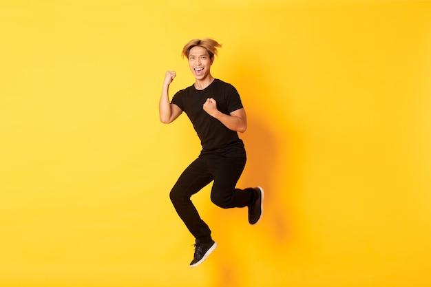 De volledige lengte van gelukkige aantrekkelijke aziatische kerel in zwarte kleren die en de overwinning springen vieren, doel bereiken, gele muur staan, zegevierend.