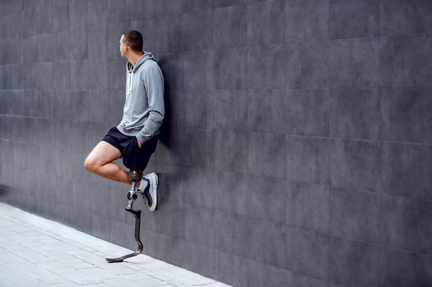 De volledige lengte van knappe kaukasische sportman met kunstbeen die buiten op de muur leunen en dient zakken in.