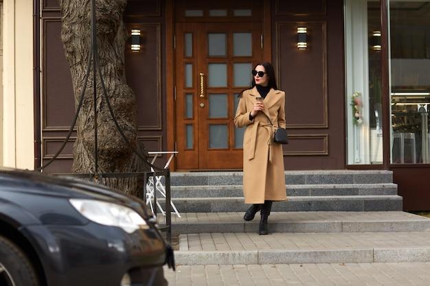 De volledige lengtefoto van mooi donkerbruin wijfje die zich dichtbij de stadsbouw bevinden, hete meeneemkoffie drinken, die naar haar auto gaan, kijkt opzij