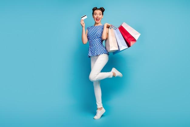 De volledige lichaamsfoto van vrij grappige dame draagt de plastic creditcard van pakken